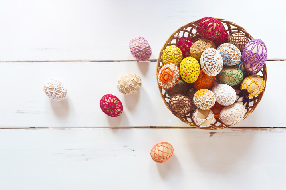 Basket full of easter eggs on a white wooden background.