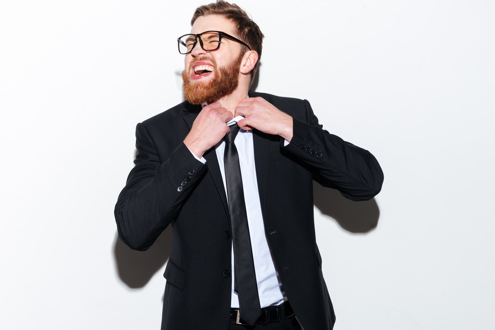 Bearded Business man in glasses unties his tie and looking aiside. Isolated gray background