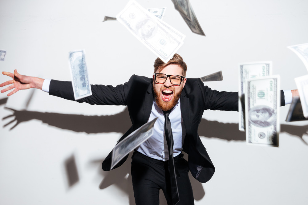 bearded business man in suit and glasses with falling money and arms