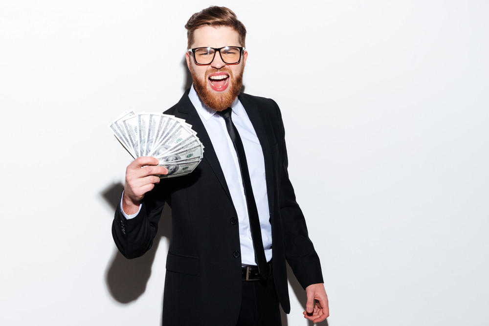 Bearded handsome Business man in glasses holding money in hand with open mouth looking at camera. Isolated gray background