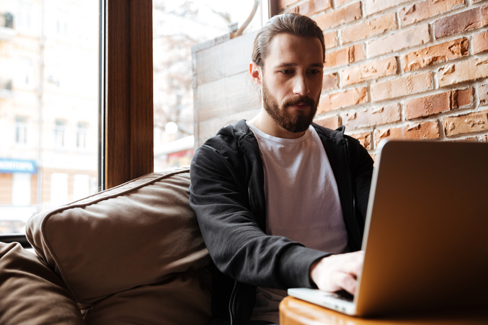 Bearded man sitting by the table and using laptop near the window in cafe
