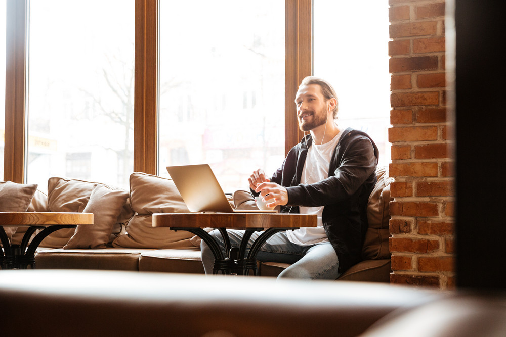 Bearded man sitting by the table near the window in cafe with laptop