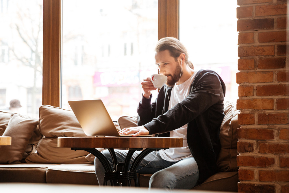 Bearded man sitting by the table with laptop and drinking coffee in cafe