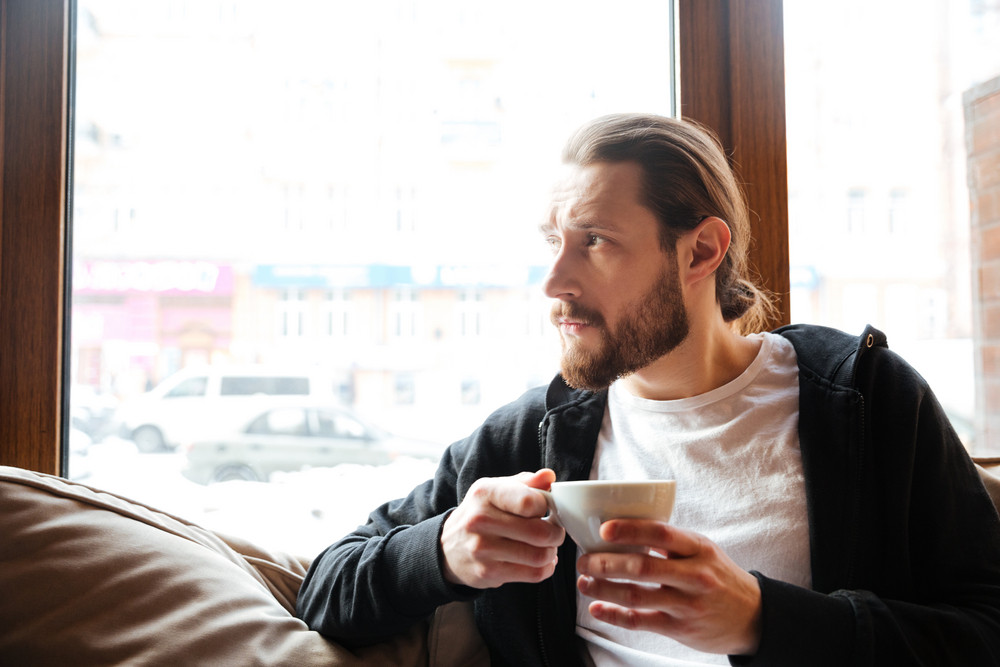Bearded man sitting in cafe near the window with cup of coffee in hands