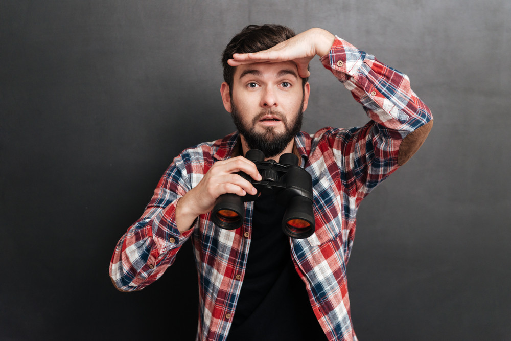 Bearded young man in plaid shirt holding binoculars and looking far away over grey background