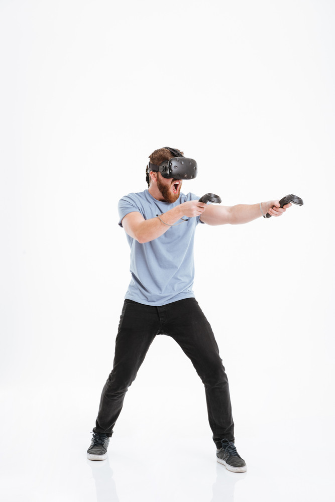Bearded young man screaming wearing virtual reality device standing over white background.