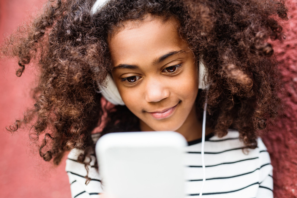 Beautiful african american girl with curly hair, holding smart phone, wearing headphones, listening music.