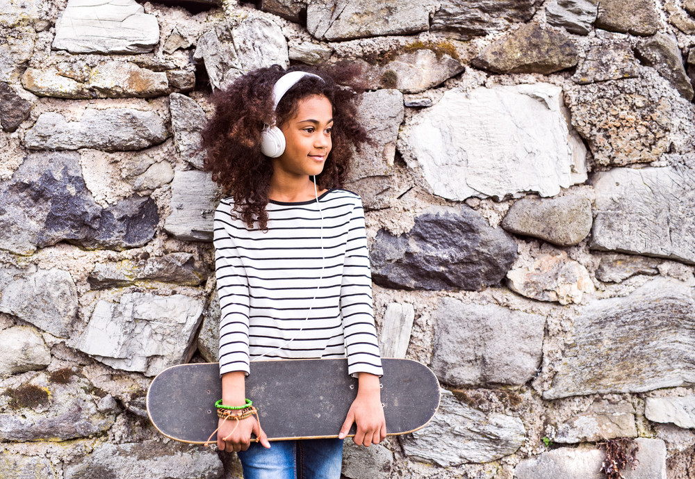 Beautiful african american girl with curly hair outdoors, against stone wall, wearing headphones, listening music.