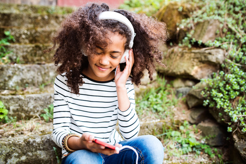 Beautiful african american girl with curly hair outdoors, sitting on stairs, holding smart phone, wearing headphones, listening music.