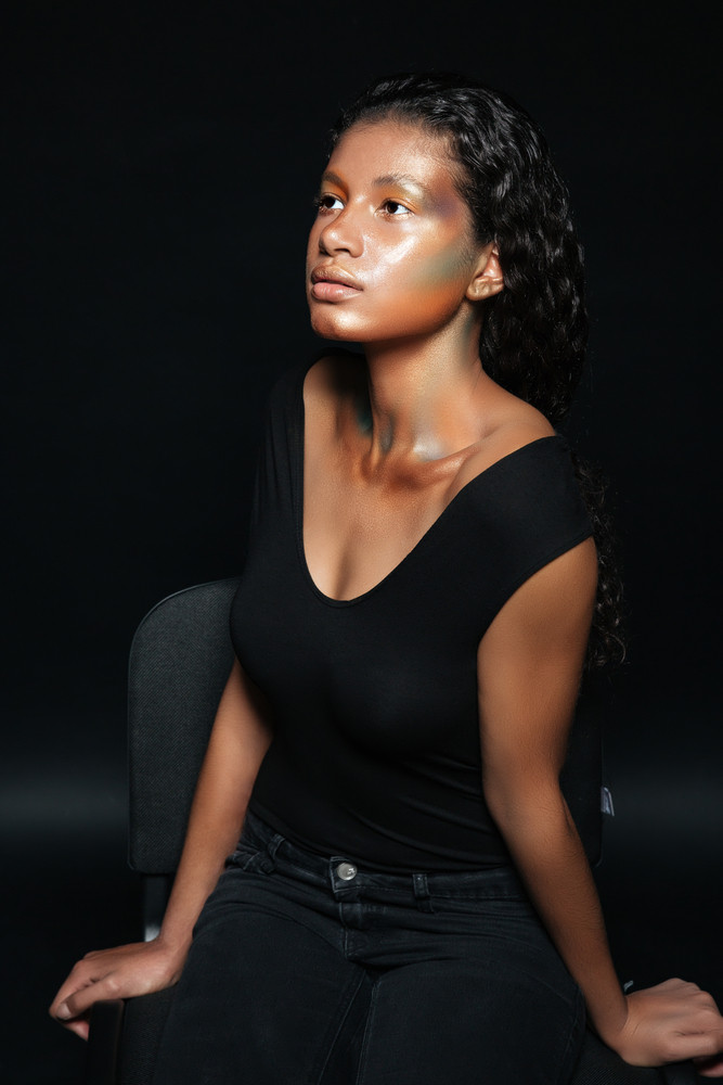 Beautiful african american young woman with shining makeup sitting on chair over black background