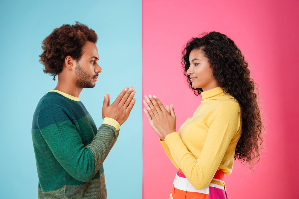 Beautiful african young couple standing with hands folded over blue and pink background