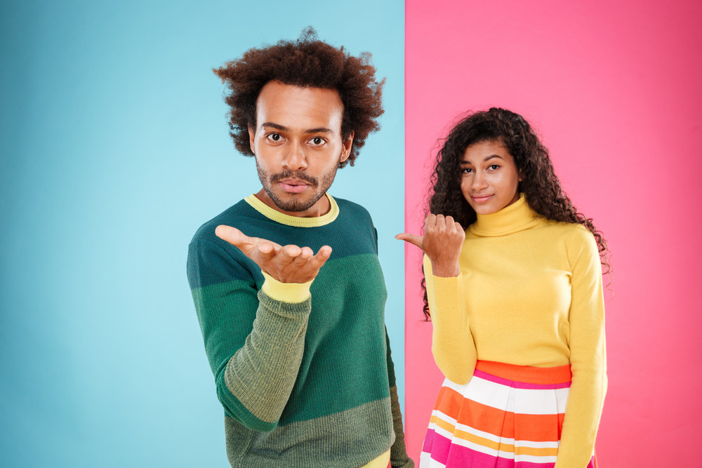 Beautiful african young woman pointing on her boyfriend who sending a kiss over colorful background