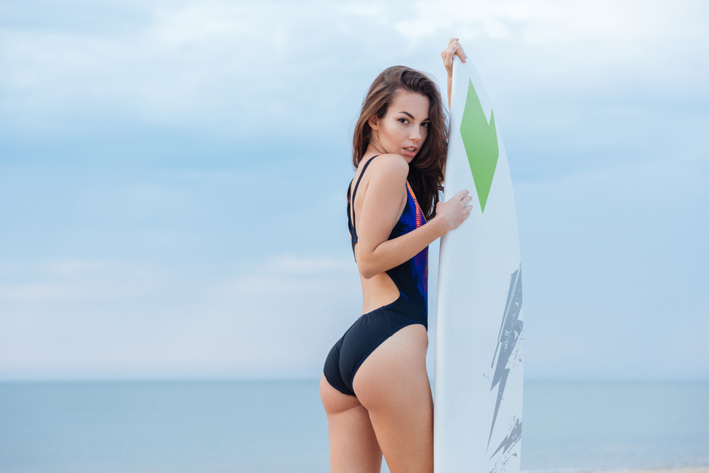 Beautiful athletic smiling girl with sexy body swimsuit having fun