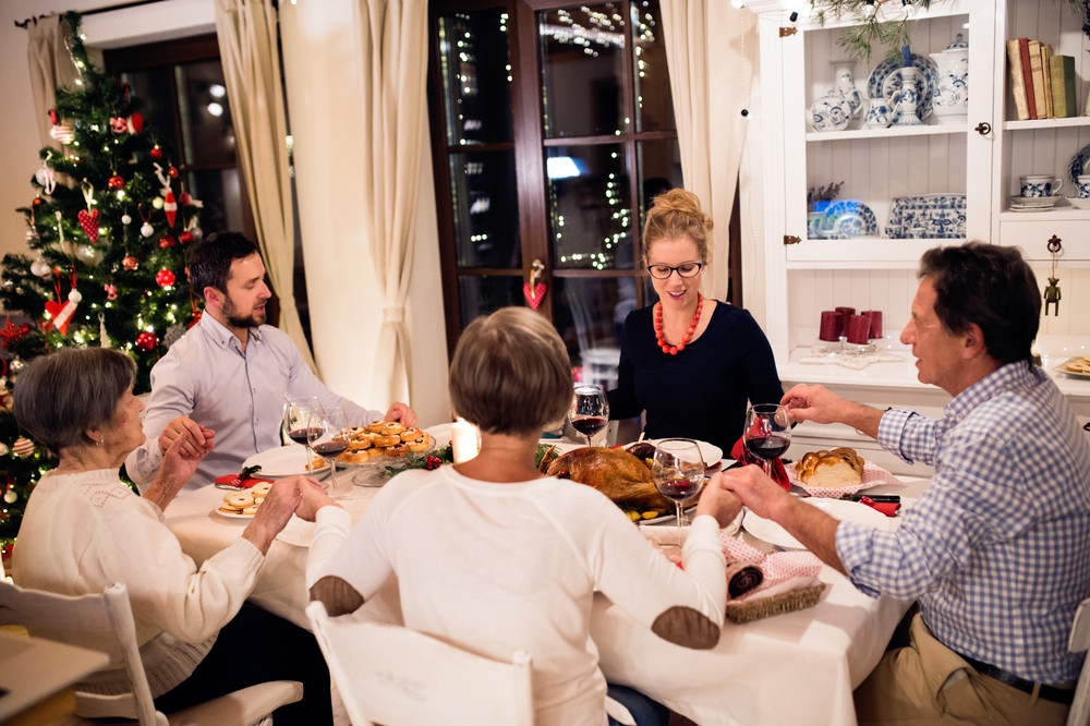 Beautiful Big Family Sitting At The Table, Celebrating Christmas Together  At Home, Holding Hands, Praying. Illuminated Christmas Tree Behind Them.