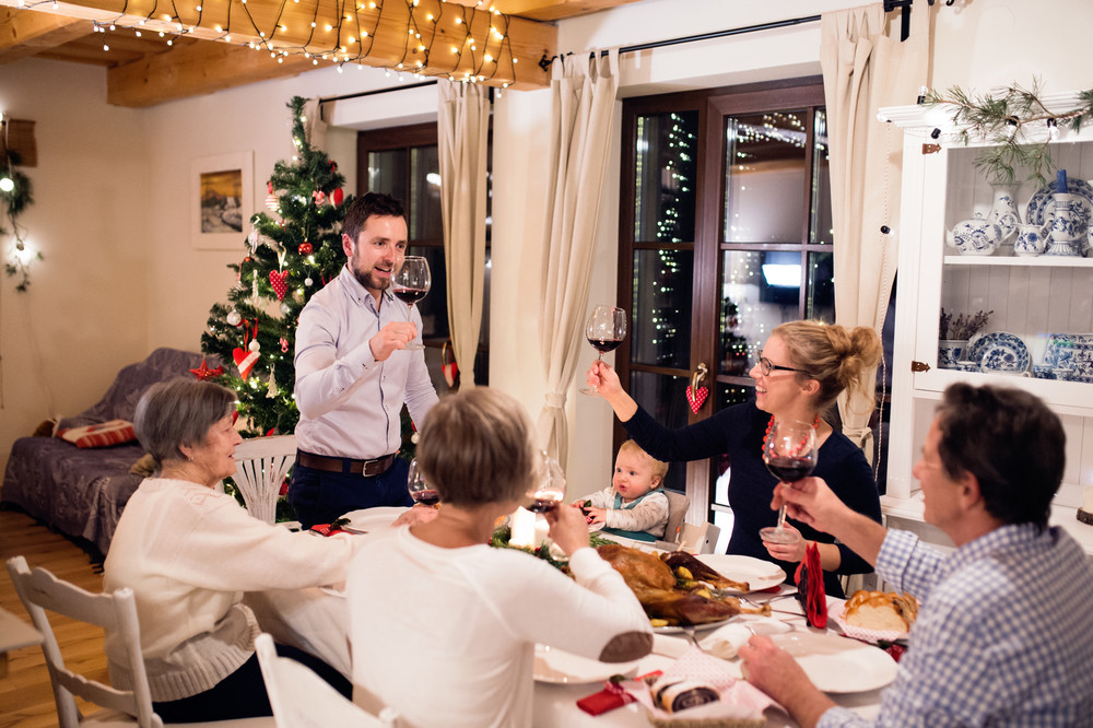 Amazing Beautiful Big Family Sitting At The Table, Celebrating Christmas Together  At Home. Illuminated Christmas Tree Behind Them.