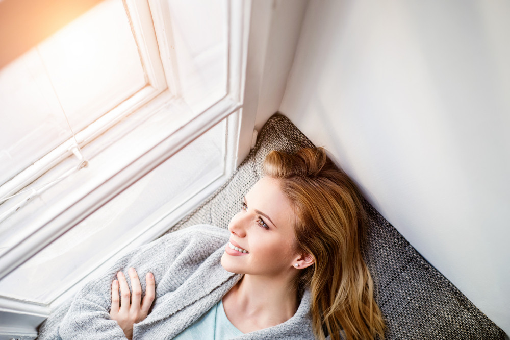Beautiful blond woman lying on window sill smiling, looking out of window
