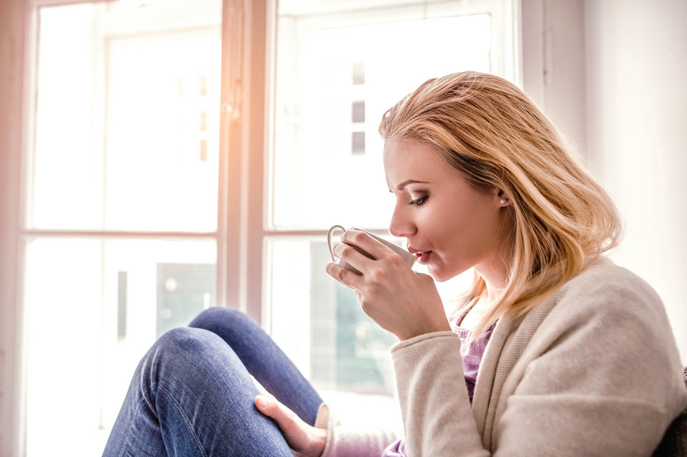 Beautiful blond woman sitting on window sill holding a cup of tea, drinking