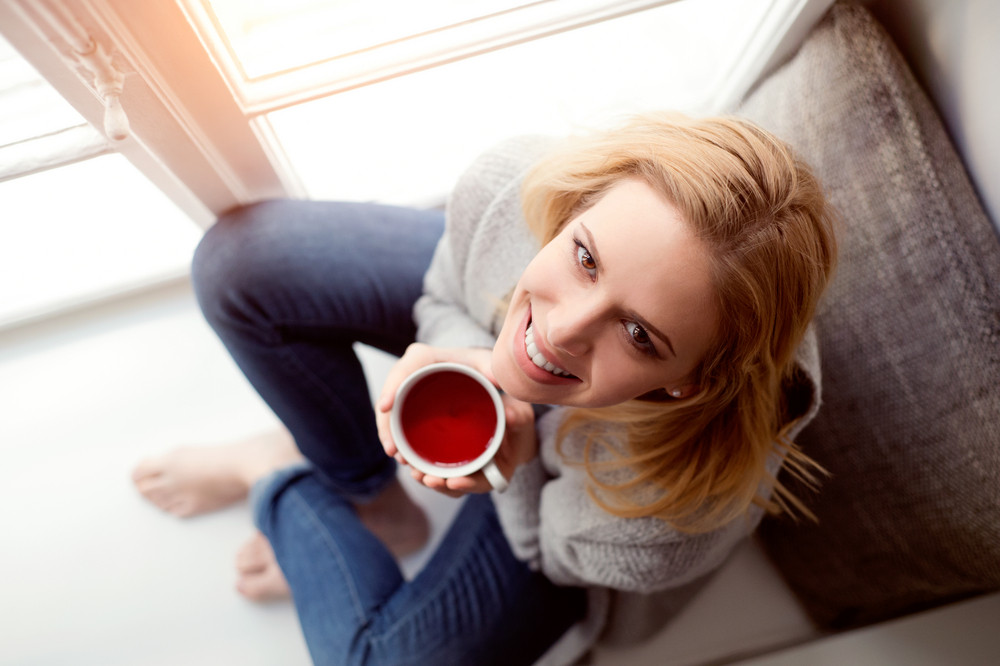 Beautiful blond woman sitting on window sill holding a cup of tea, high angle view