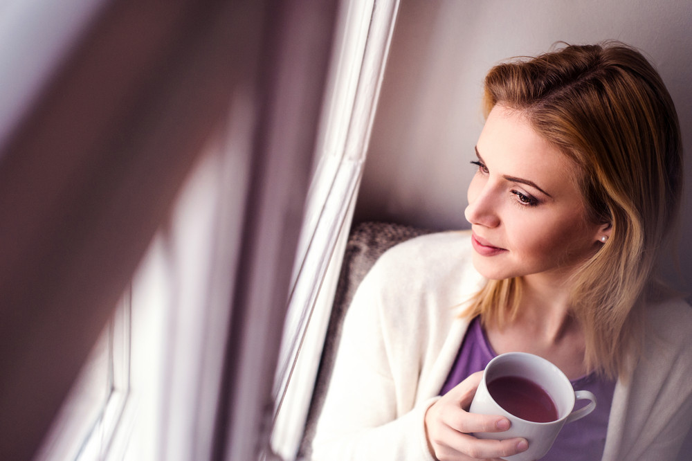 Beautiful blond woman sitting on window sill holding a cup of tea, looking out of window