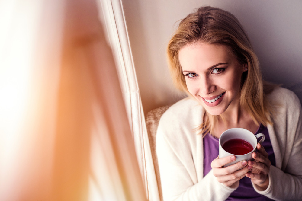Beautiful blond woman sitting on window sill holding a cup of tea