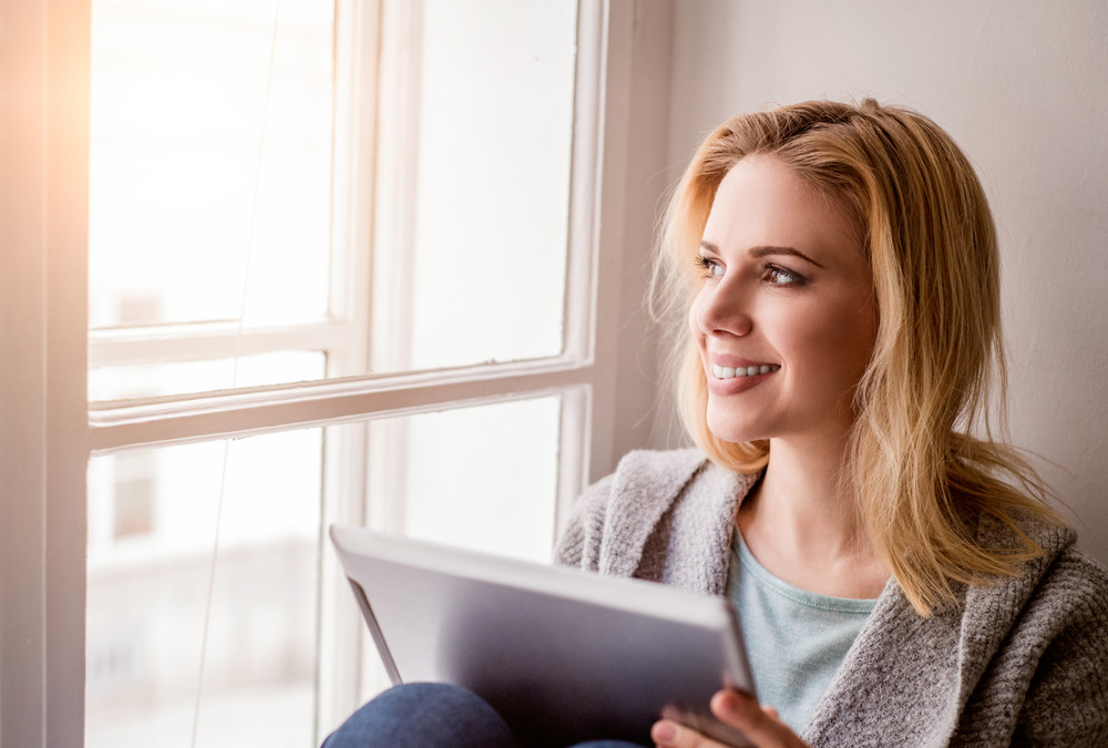 Beautiful blond woman with tablet sitting on window sill, sunny day