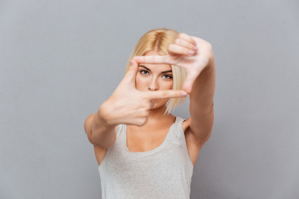 Beautiful blonde young woman making frame with fingers over gray background