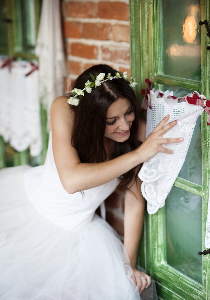 Beautiful bride in country style wedding dress is looking out of the window