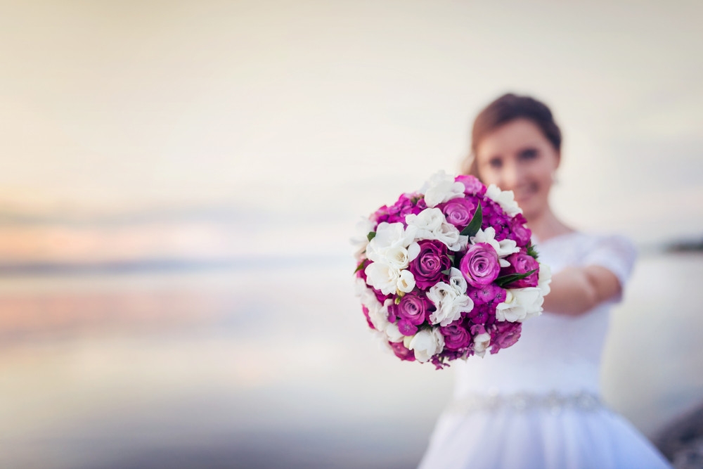 Beautiful bride with bouquet standing on the beach