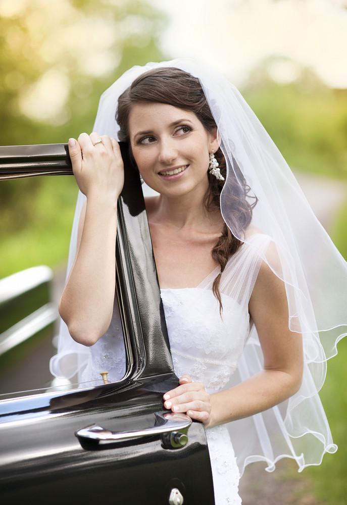 Beautiful Bride with retro car. Outdoor wedding portrait.