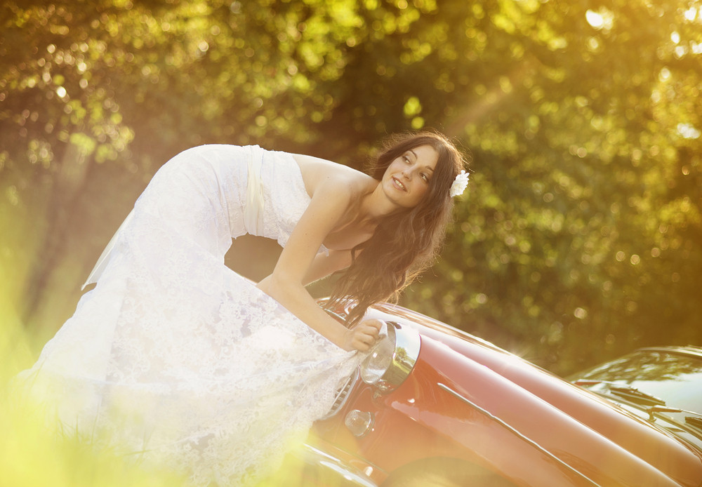 Beautiful brunette bride on a green meadow with retro car