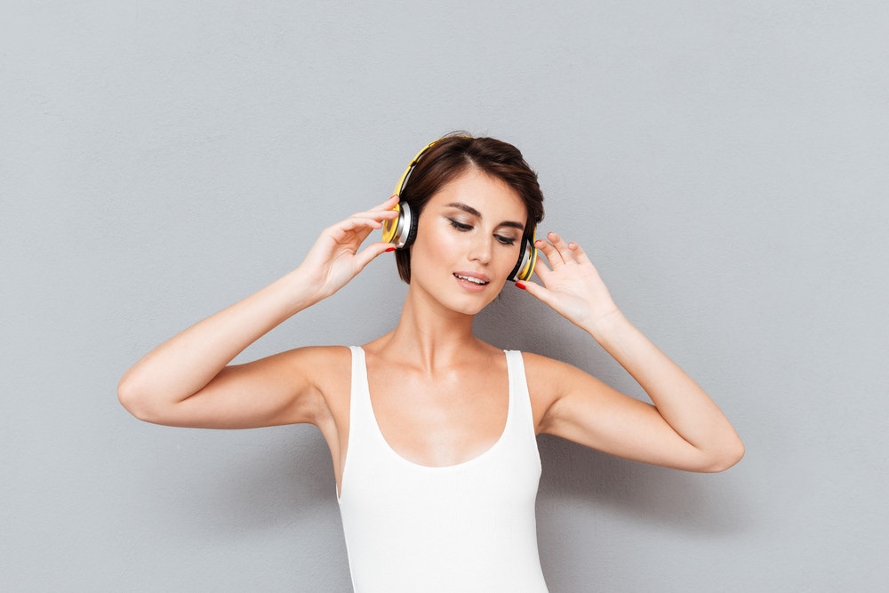 Beautiful brunette young woman listening to music with headphones isolated on gray background