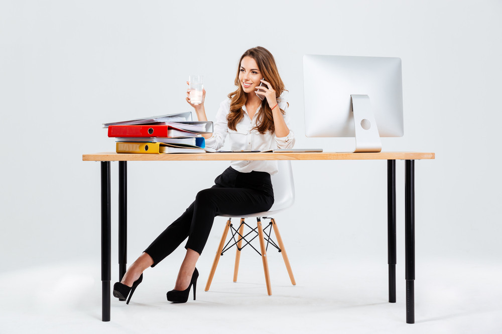 Beautiful businesswoman sitting at the desk with water glass in hand and talking on the phone isoltaed on the white background