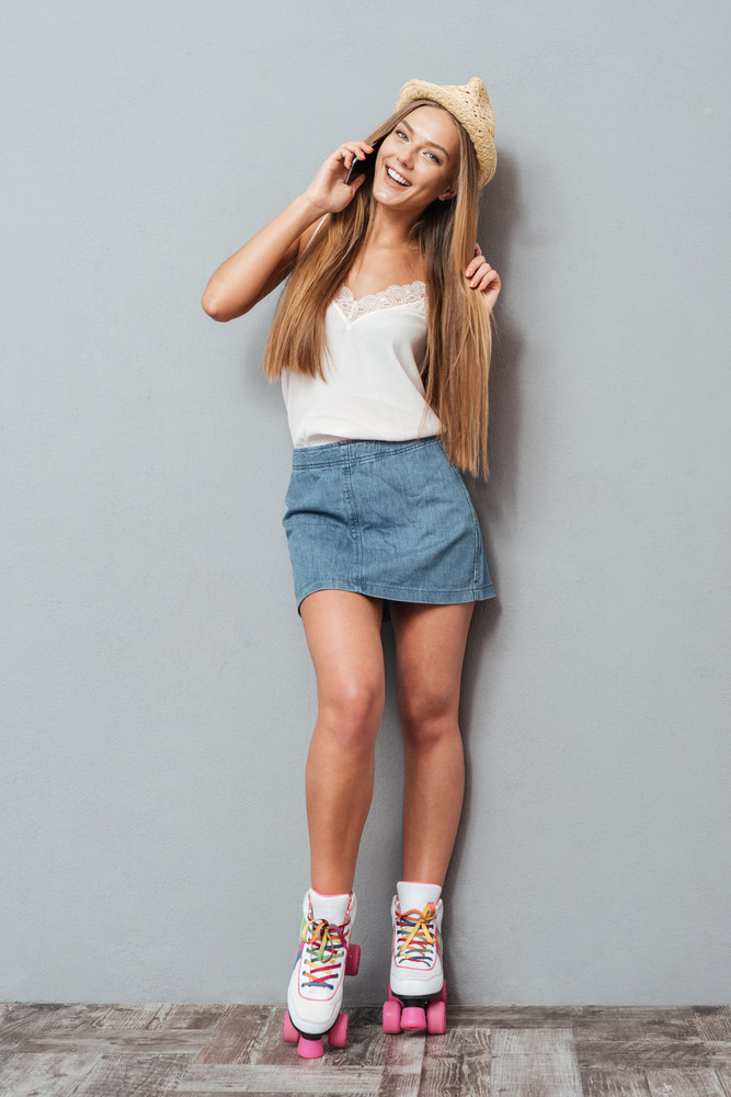 Beautiful charming girl in hat and roller skates talking on the phone isolated on a gray background