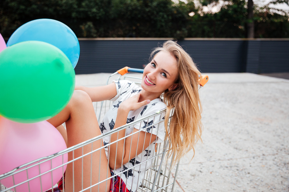 Beautiful cheerful girl sitting in shopping cart and holding color balloons outdoors