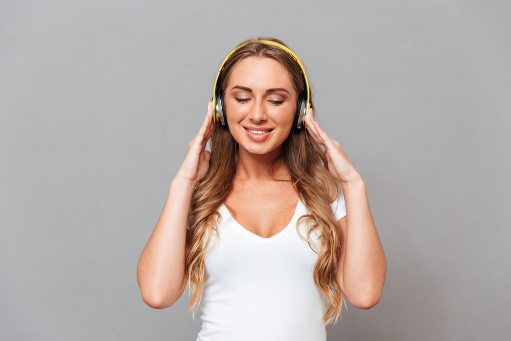 Beautiful cheerful smiling woman listening to music with headphones and eyes closed isolated on gray background
