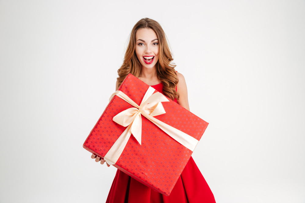 Beautiful cheerful woman in santa claus dress giving you big red gift over white background