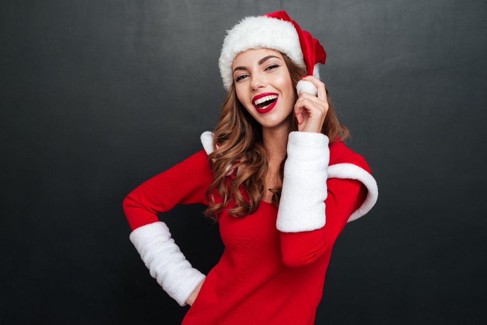 Beautiful christmas woman looking at the camera and holding her hat