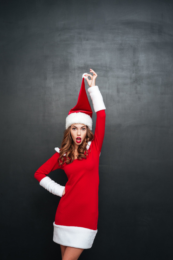 Beautiful christmas woman looking at the camera and holding her pompon hat over black background