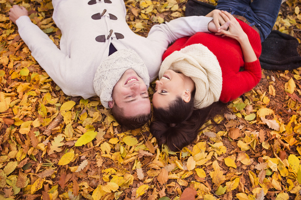 Beautiful couple lying on the ground in colorful autumn leaves.
