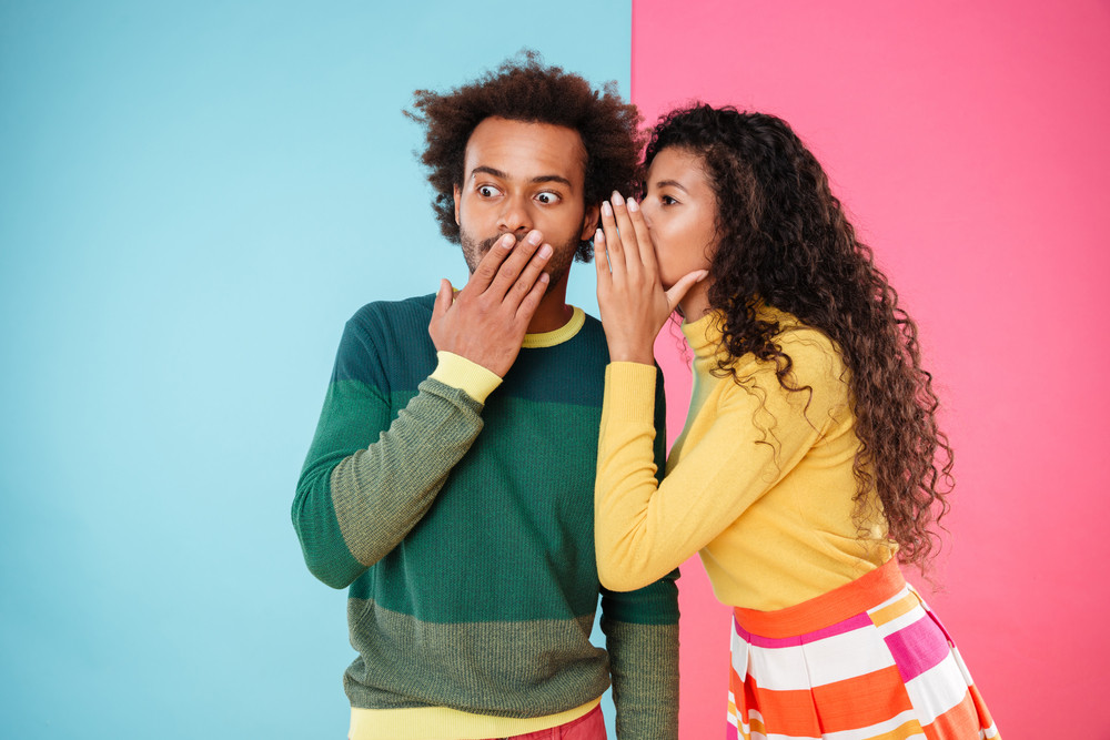 Beautiful curly young woman telling secrets to her boyfriend over colorful background