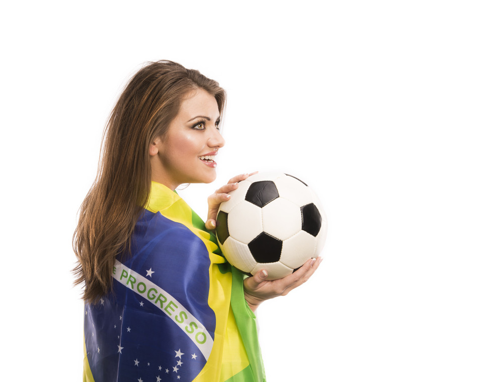 Beautiful female fan with brazilian flag holding a soccer ball isolated on white background