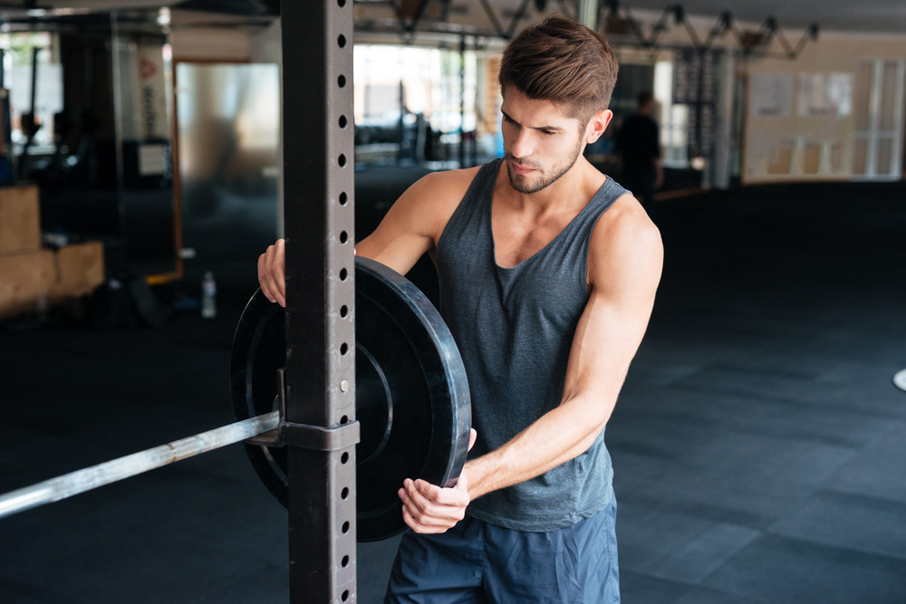 Beautiful fitness man with barbells. thoughtful
