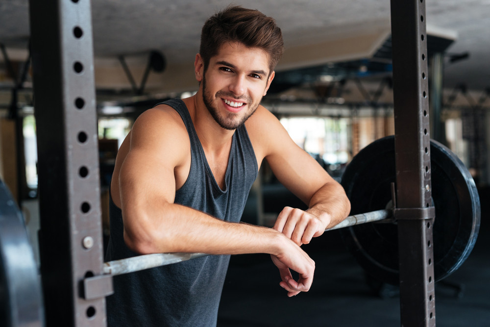 Beautiful fitness man with weights. Smiling.
