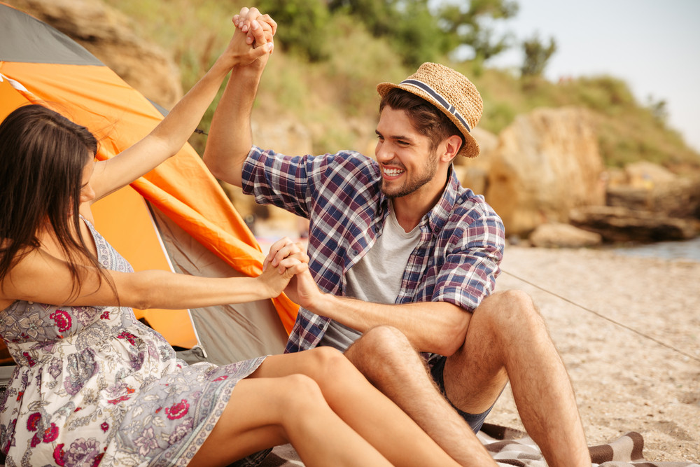 Beautiful girl and handsome man playing fighting at the beach while camping