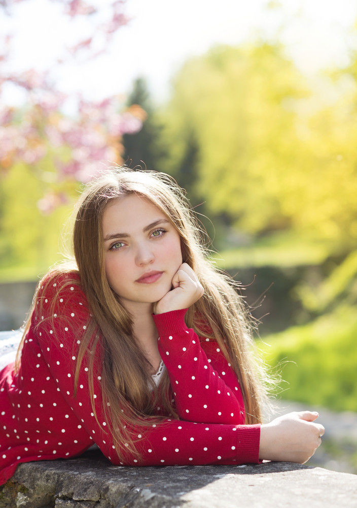 Beautiful girl in red cardigan lying on a wall in spring garden with blooming trees