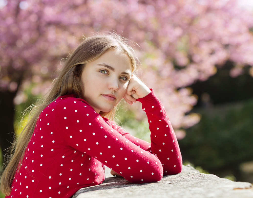 Beautiful girl in red cardigan lying relaxing in spring garden with blooming trees