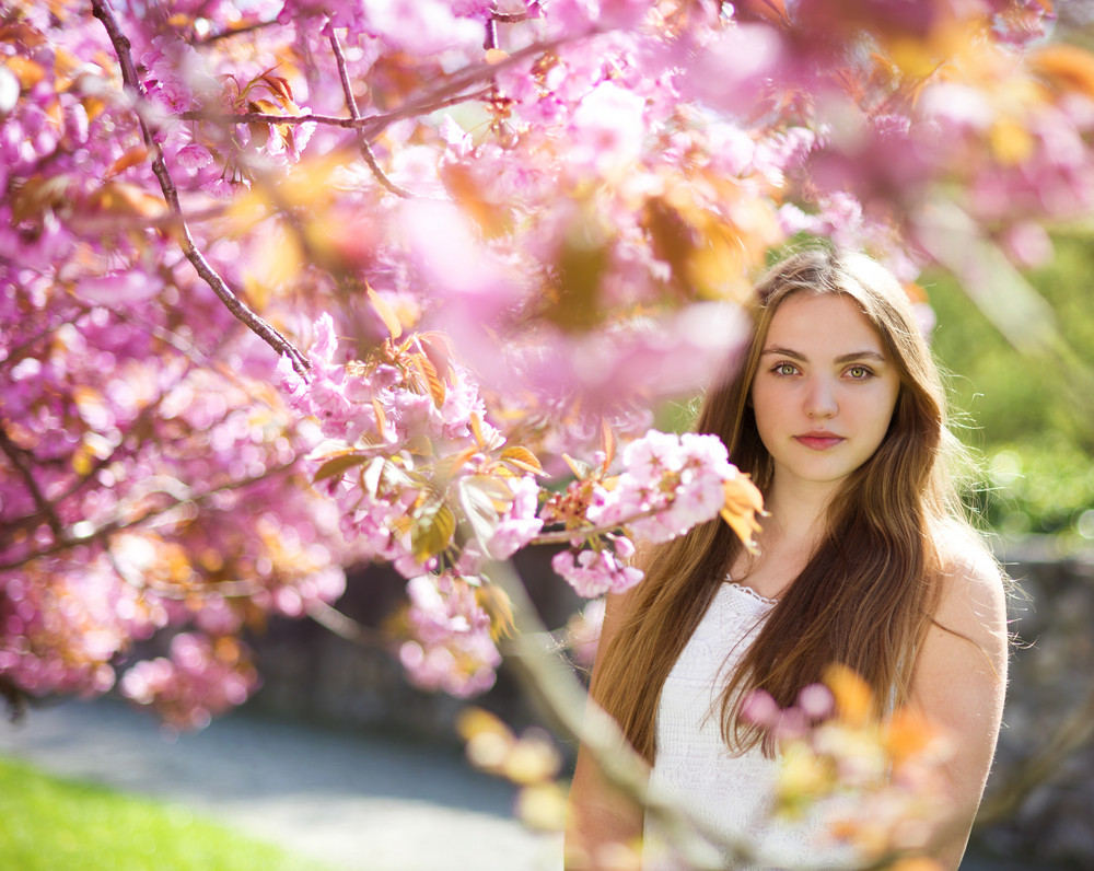 Beautiful Girl In Spring Garden Among The Blooming Trees With Pink