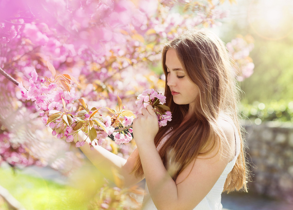 Beautiful girl in spring garden among the blooming trees with pink flowers