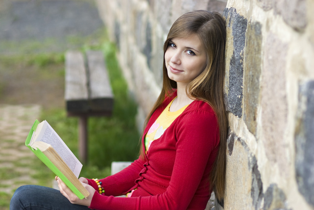 Beautiful girl is reading book.