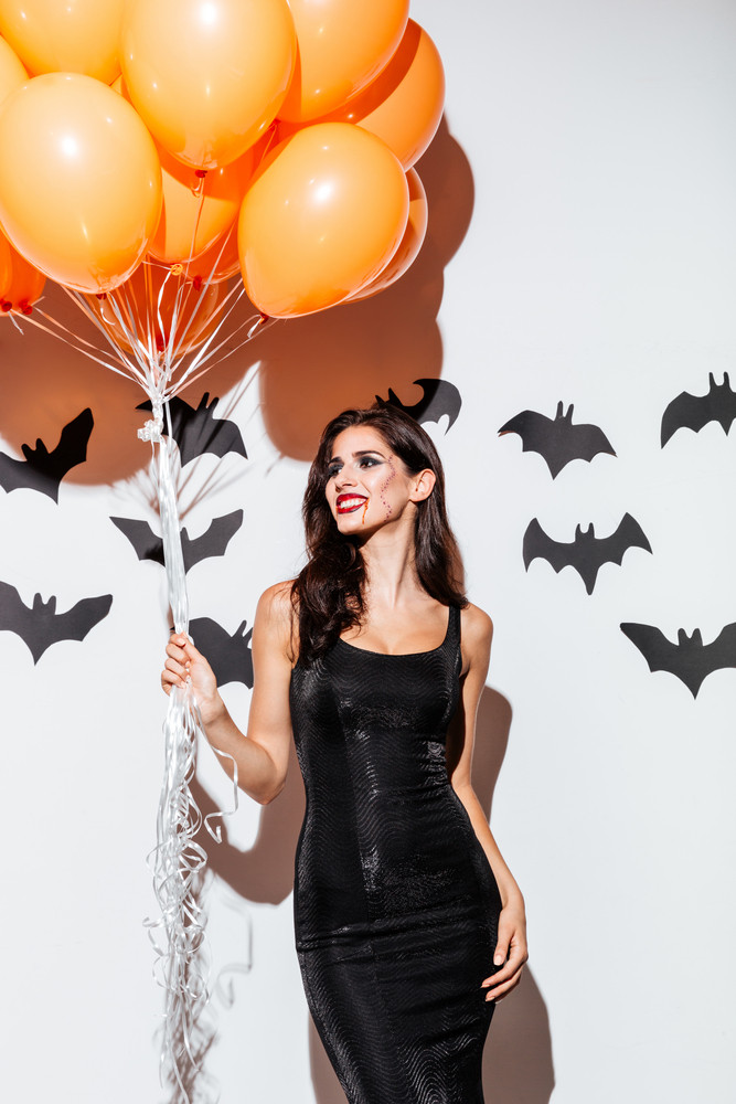 Beautiful gothic brunette girl in black halloween costume holding orange balloons isolated on the white background